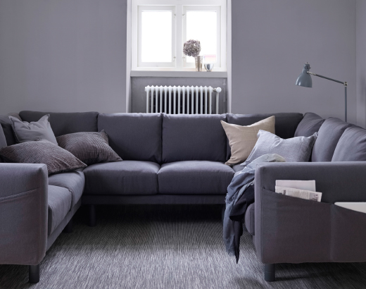 A living room with a dark grey U-shaped 8-seat sofa with grey legs.