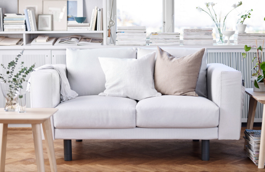 A light living room with a white two-seat sofa with grey legs.