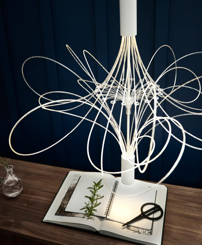A modern chandelier with steel tubes with LEDs that creates exciting lighting effects and looks like the path of fireflies flying in the air.