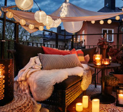 A cosy balcony with lit LED lighting chains, a canopy, lanterns with lit candles and a sofa filled with cushions and sheepskin rugs.""