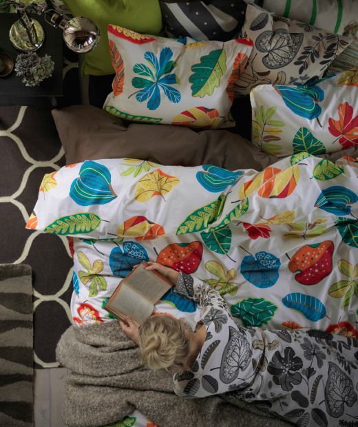 A colourful quilt cover with leaf pattern and two pillowcases seen from above.