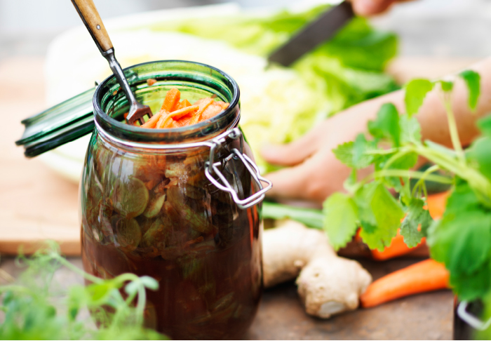 A glass jar with aroma-tight seal filled with pickled vegetables.
