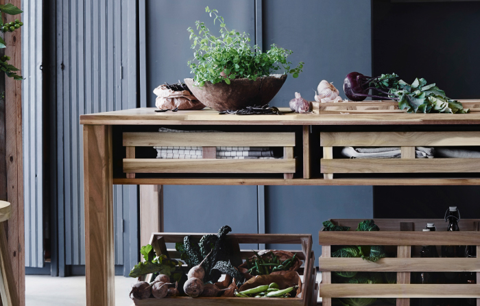A bar table in solid acacia with storage crates filled with vegetables.