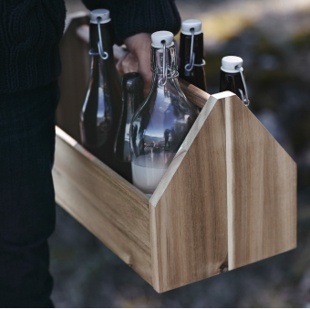 A storage box in solid acacia filled with glass bottles.