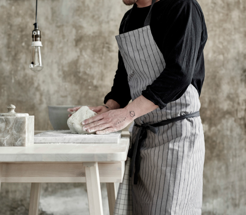A man wearing a grey apron with dark grey stripes.