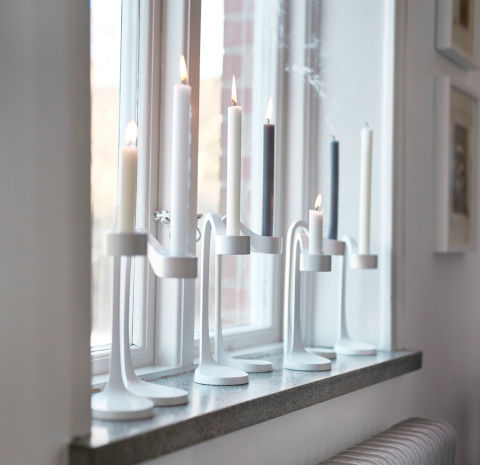 Several white candle holders with lit candles on a windowsill.