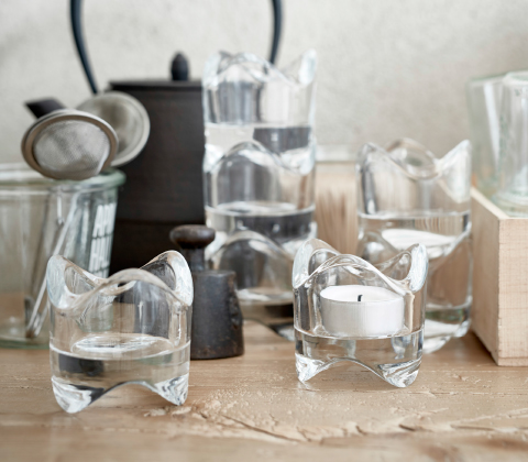Several tealight holders in clear glass on a worktop.