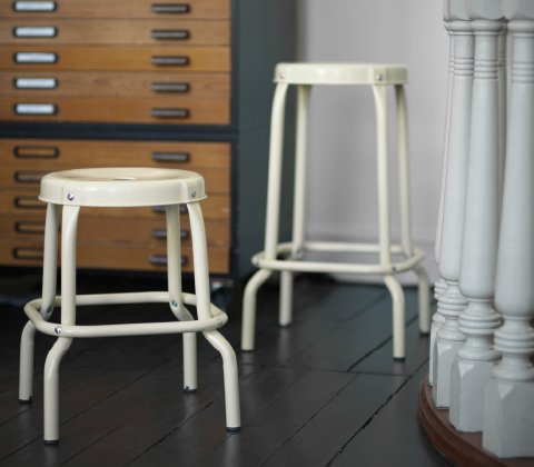 A stool and a bar stool, both in beige powder coated steel.