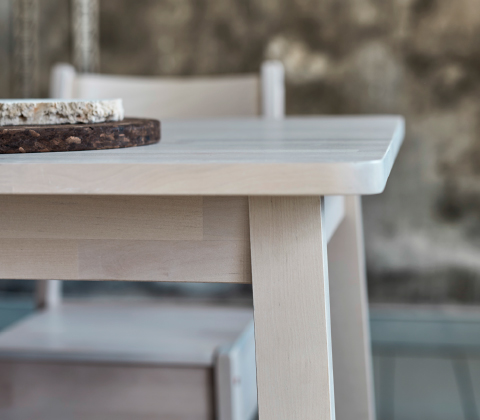 A close-up of a dining table in white stained birch.