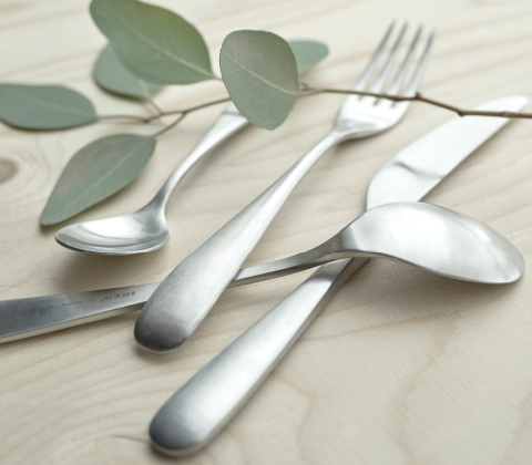 A close-up of a stainless steel cutlery set consisting of forks, knives, spoons and teaspoons, 6 of each