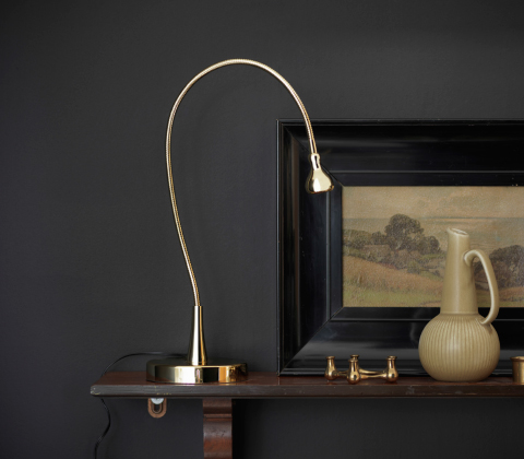 A slim gold-coloured work lamp with a bendable arm.