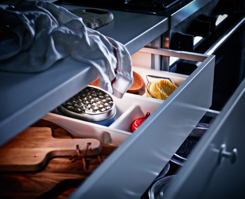 An open kitchen drawer with a lit LED lighting strip.