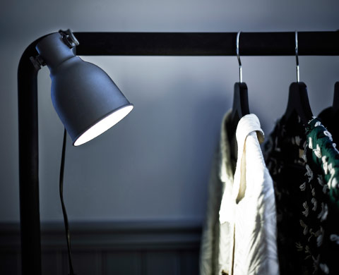 A lit clamp spotlight attached to a clothes rack.