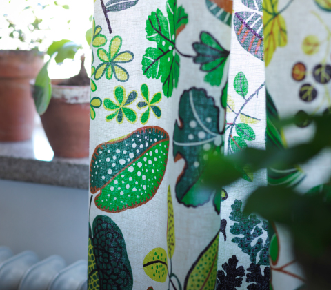 A close-up of a colourful curtain with leaf pattern.