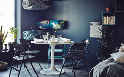 Dining areas needn't be formal and static. With some fold away chairs, an adjustable table and soft, roll-up mattress close at hand (stored on the wall) it's easy to create a dining area to suit you.""