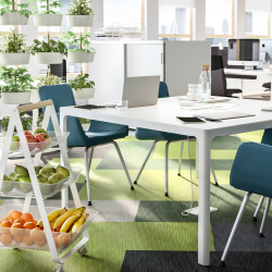 An open plan office with a white conference table combined with conference chairs in turquoise wool cover.