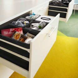 An open kitchen drawer with black waste sorting bins.