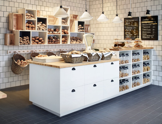 A bakery with open wall shelves filled with newly baked bread and a bench with drawers and open shelves.
