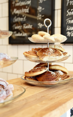 A serving stand with three tiers filled with buns and sweet crisp biscuits.