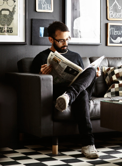A man sitting in a leather sofa reading a newspaper.