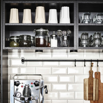 Open wall cabinets filled with mugs and glass jars with different kinds of tea.