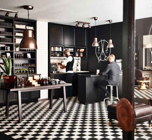 A hairdressing saloon furnished with black-brown kitchen cabinets.