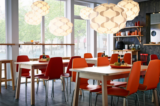 A restaurant furnished with tables in white stained birch combined with chairs in orange with chrome legs.