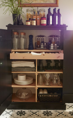 An open cabinet with shelves and drawers inside filled with candle holders, plates and tablecloths.