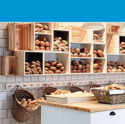 A bakery with open wall shelves filled with newly baked bread.