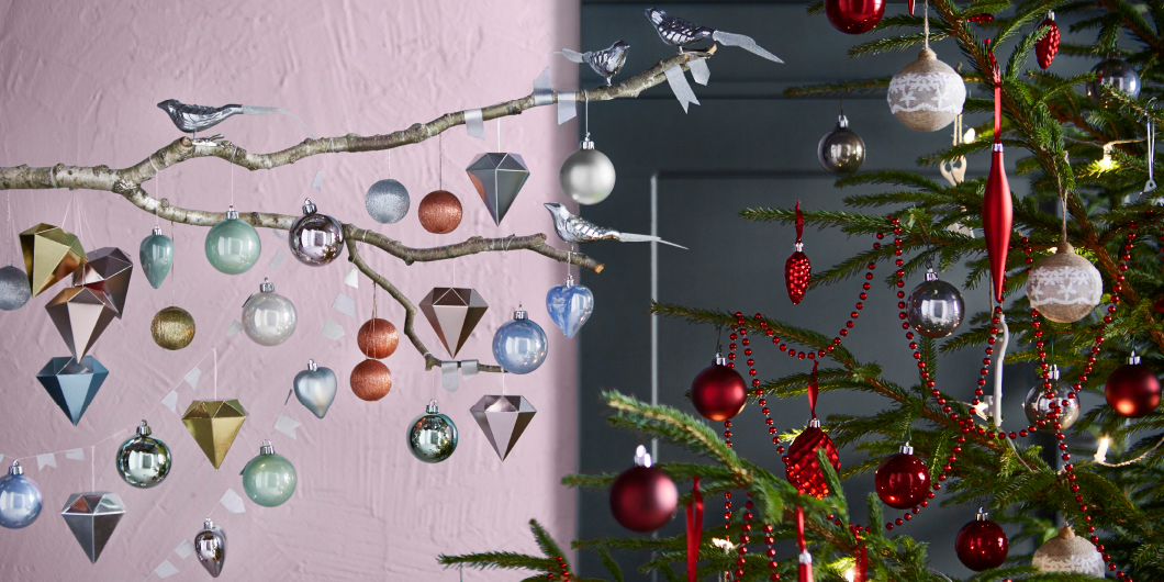 A branch with pastel coloured baubles and silver-coloured birds together with a Christmas tree decorated with baubles and cones in red and beige.