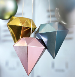 Close-up of diamond-shaped hanging decorations in pastel colours.