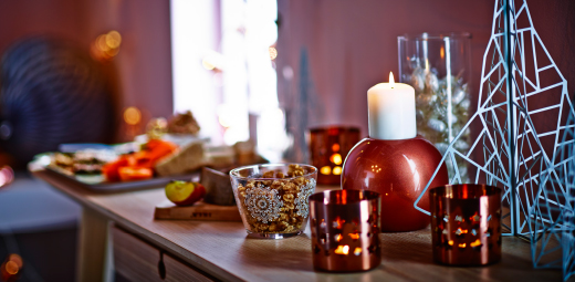 A sideboard with copper-coloured candle holders, tealight holders and glass bowls filled with candy.