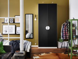 A bedroom with a white wardrobe with black doors combined with a black bed and a green glass-door cabinet.
