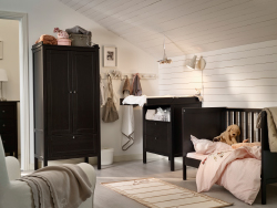 A nursery with a cot, changing table and wardrobe, all in black-brown.
