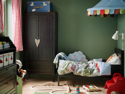 A children's room with an extendable bed, wardrobe and a chest of drawers, all in black-brown.