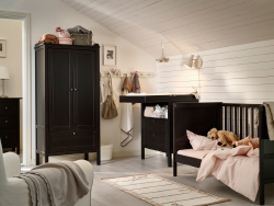 A nursery with a crib, changing table, and wardrobe, all in black-brown.