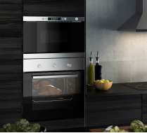Stainless steel oven, microwave oven and extractor hood in a black wood effect kitchen with brown-black worktops.