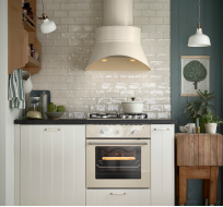 Beige extractor hood and oven in an off-white kitchen with black worktops and white porcelain handles.
