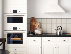 Off-white oven, microwave oven and extractor hood in an off-white kitchen with black mineral effect worktops, white porcelain knobs and chrome-plated handles.