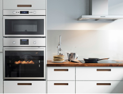 Stainless steel oven, microwave oven and extractor hood in a white kitchen with worktops in walnut.