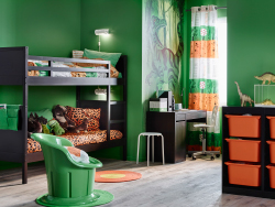 A children's room with black bunk bed, desk, storage and textiles in green and orange.