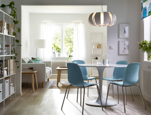 A dining room with a round white dining table combined with light blue chairs with stainless steel legs.