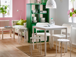A small apartment with a dining area with a white small table, two chairs and two stools and a green shelving unit used as a room divider.