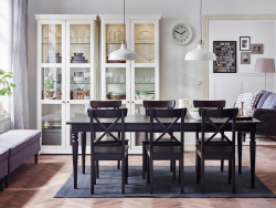 A large dining room with a black extendable dining table with chairs and glass-door cabinets in white.