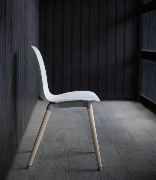 A chair with a white seat and birch legs, seen from the side.