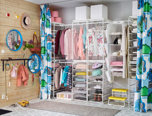 A hallway with a large storage solution consisting of frames, wire baskets and clothes rods in white powder coated steel.