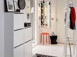A white hallway with white shoe cabinets on the wall combined with a hat/coat stand.