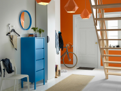A hallway with a blue chest of 4 drawers with a blue mirror hanging above. Combined with a white wardrobe and orange pendant lamps.