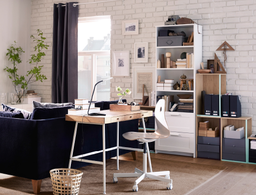 A home office inside the living room consisting of a desk in bamboo with white steel legs, a white swivel chair on castors and storage in white and bamboo.