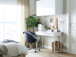 A white desk with a black swivel chair on castors and a wall cabinet, inside the bedroom.